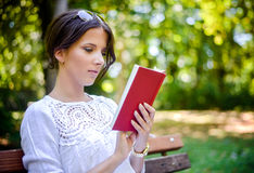Woman reading an interesting book in the park Royalty Free Stock Photos