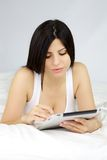 Woman reading ipad tablet in bed  Stock Images