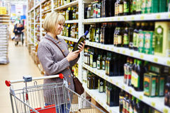Woman reading label on bottle of olive oil in store Royalty Free Stock Image