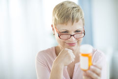 Woman Reading Label On Pill Bottle Stock Photo