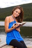 Woman reading by a lake Stock Photos