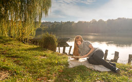 Woman reading by the lake Royalty Free Stock Photo