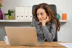 Woman reading laptop in office Stock Image