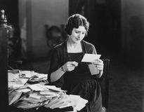 Woman reading letter with pile of mail Stock Photos