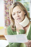 Woman Reading Letter After Receiving Neck Injury Royalty Free Stock Image