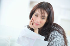 Woman reading letter and smiling Royalty Free Stock Photos