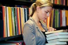 Woman reading in a library. Serious attractive woman with a stack of books in her arms standing reading in a library with bookshelves full of books Stock Images