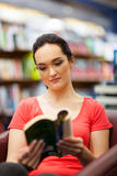 Woman reading in library. Young woman reading book in library Royalty Free Stock Image