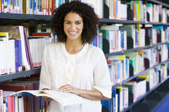 Woman reading in a library. Woman reading book in a library Royalty Free Stock Photos