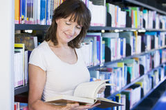 Woman reading in a library Stock Photos