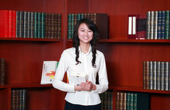 Woman reading in library. Asian  young woman reading in library Royalty Free Stock Photos