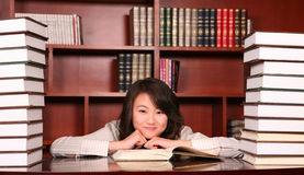 Woman reading in library. Asian  young woman reading in library Royalty Free Stock Photo