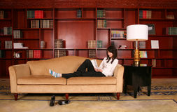 Woman reading in library. Asian  young woman reading in library Royalty Free Stock Photography