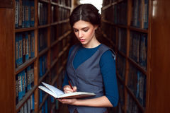 Woman reading in a library. Bookshelves with books on the backgroung Stock Images