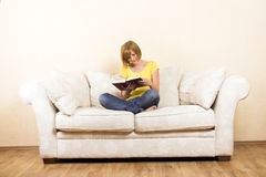 Woman is reading on a lounge Royalty Free Stock Images