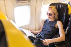 Woman reading magazine on airplane during flight. stock images
