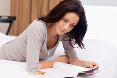 Woman reading a magazine on the bed Royalty Free Stock Image