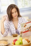 Woman reading magazine at breakfast Stock Images