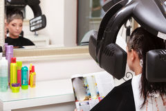 Woman reading magazine in hair beauty salon. By hairdresser. Royalty Free Stock Photos