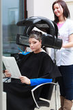 Woman reading magazine in hair beauty salon. By hairdresser. Stock Photo