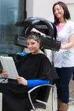 Woman reading magazine in hair salon Stock Photography