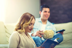 Woman reading magazine. Happy young man sitting on the sofa watching TV Stock Photography