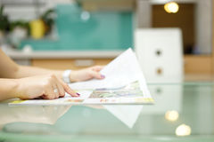 Woman is reading magazine  in the kitchen Royalty Free Stock Photo