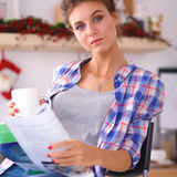Woman reading magazine In kitchen at home Royalty Free Stock Images