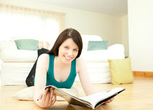 Woman reading a magazine lying down on the floor royalty free stock image