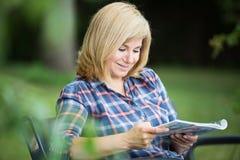 Woman reading magazine royalty free stock images