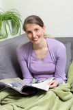 Sitting woman. Woman reading magazine while sitting on the couch Stock Image