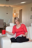 Woman reading magazine on sofa. A young blond woman sitting on a sofa reading a magazine and holding a tea mug Royalty Free Stock Photo