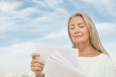 Woman Reading Mails Against Sky Stock Photos
