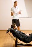 Woman reading man lying on chaise longue. Woman reading men lying on chaise longue in studio royalty free stock photo