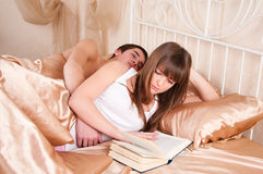 Woman reading and  man sleeping next to her. Woman reading a book and  man sleeping next to her Royalty Free Stock Images
