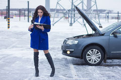 Woman reading a manual car and standing near her broken car. Beautiful Woman reading a manual car and standing near her broken car Royalty Free Stock Photos
