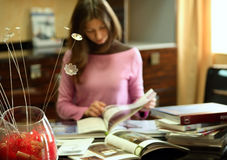 Woman reading many books indoors. Woman reading books indoors, focus on artificial flower Stock Photos