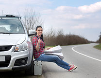 Woman reading map beside car Stock Image