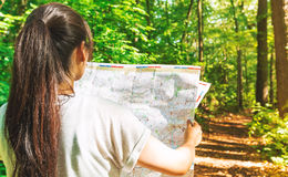 Woman in reading a map in the forest Royalty Free Stock Photo