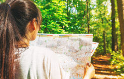 Woman in reading a map in the forest Royalty Free Stock Photos