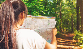 Woman in reading a map in the forest Royalty Free Stock Photography