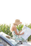 Woman reading map while leaning on convertible Royalty Free Stock Photo