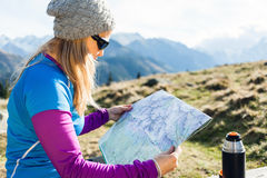 Woman reading map in mountains. Young woman hiker reading map in mountains on hiking trip, Tatra Mountains in Poland Stock Images