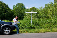 Woman reading a map by the roadside with blank sig Royalty Free Stock Images