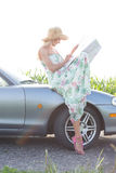 Woman reading map while sitting on convertible Royalty Free Stock Images