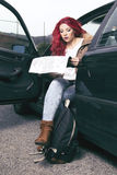 Woman reading a map, sitting in her black car. Red haired woman, reading a road map, sitting in her black car with her backpack. Ready to adventure Stock Photos