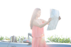 Woman reading map while standing by convertible against clear sky Stock Photos