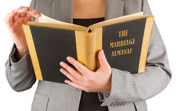 Woman reading a marriage almanac. Saving her marriage Royalty Free Stock Photography