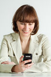 Woman reading message. Middle aged woman reading message on her smartphone Stock Image