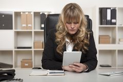 Woman reading a message on her tablet at work Royalty Free Stock Image